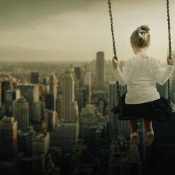A child playfully swinging above the skyscrapers of a city business district